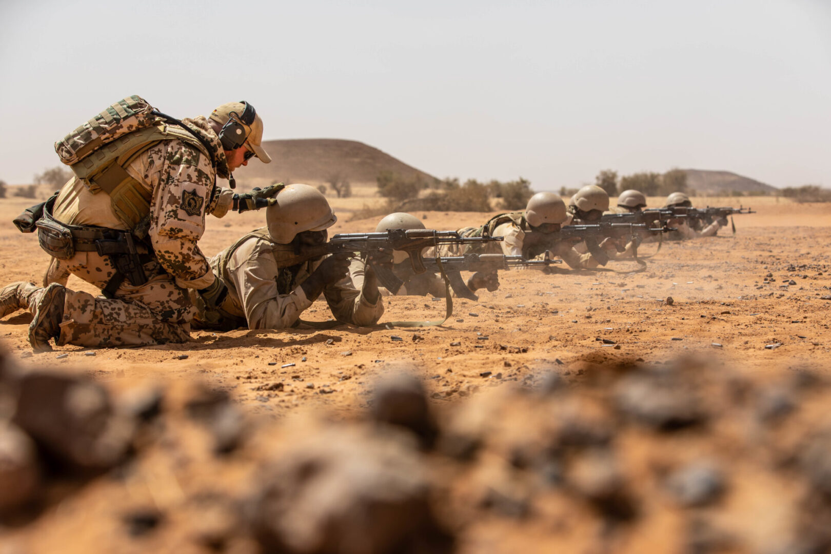 A German Armed Forces instructor coaches Mauritanian soldiers refining their marksmanship skills during Flintlock 20 near Kaedi, Mauritania, Feb. 12, 2020. Since 2005, nations from throughout Africa, Europe, North America and elsewhere have come together to conduct Flintlock exercises in austere environments to work and train together with one clear goal: to help improve conditions and the capabilities of partner nations so the people in this region can pursue a life free from violence.  (U.S. Army photo by Spc. Wheeler Brunschmid.)